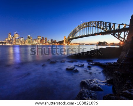 Sydney city cbd and harbour bridge view at sunset with illumination of lights at low tide Australia - stock photo