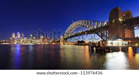 Sydney city CBD view across harbour along Bridge illuminated at sunset lights reflected in water australia landmarks - stock photo