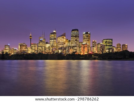 SYdney city CBD view from Royal Botanic Garden at sunset when skyscraper illumination is full on and bright lights reflecting in blurred still waters of Sydney Harbour - stock photo
