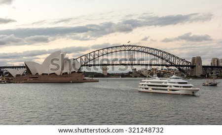 SYDNEY - DECEMBER 27, 2013: Sydney Boat Tour Harbour Cruise in Circular Quay under Sydney Harbour Bridge near Sydney Opera House under Dramatic Golden Sky at Sunset - stock photo