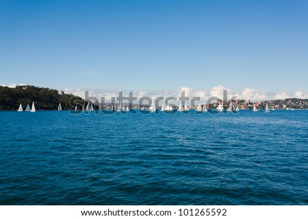 Sydney Harbour Skyline, with kids sailing in sailboats - stock photo