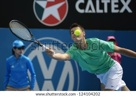 SYDNEY - JAN 9: Bernard Tomic from Australia stretches for a forehand in his second round match in the APIA Sydney Tennis International. Sydney January 9, 2013. - stock photo