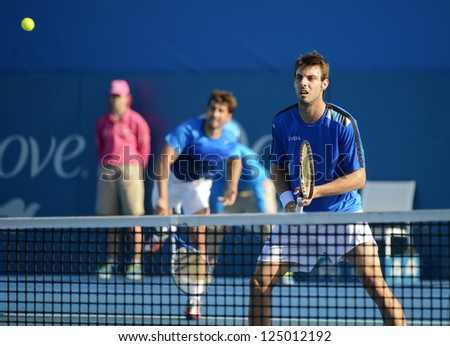 SYDNEY - JAN 11: Marcel Granollers at the net with partner Marc Lopez serving in their doubles semi final at the APIA Sydney Tennis International. Sydney January 11, 2013. - stock photo