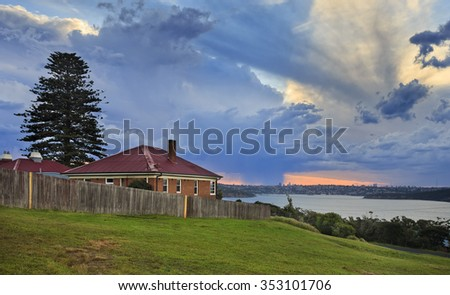 Sydney North head hill with historic cottage building behind aged wooden fence overlooking inner harbour seascape with stormy rain clouds at sunset - stock photo