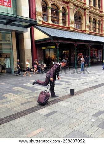 """SYDNEY, NSW, AUSTRALIA - January 10, 2015: A street performer dressed as a tourist """"living statue"""" entertains passers-by, Sydney. - stock photo"""