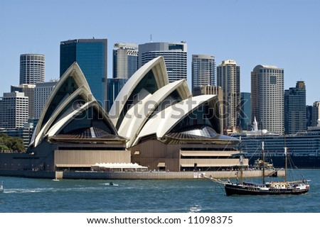 sydney opera house with city skyline in background and pirate ship in foreground taken from harbor - stock photo