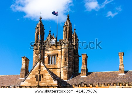 Sydney Uni building facade with Australian flag. University of Sydney against deep blue sky with white clouds, daytime photo - stock photo