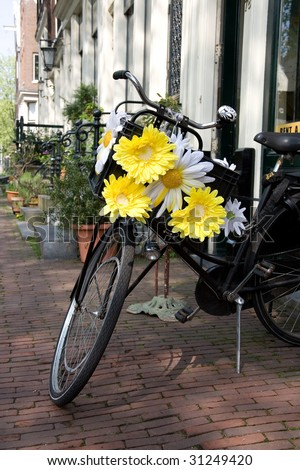 Symbol of Amsterdam, bicycle decorated with white and yellow flowers - stock photo