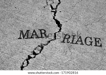 Symbol of broken marriage with crack in concrete and word - stock photo