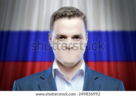 Symbol of censorship and freedom of speech: a young man without a mouth on a background of the national flag of Russia - stock photo