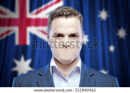 Symbol of censorship and freedom of speech: a young man without a mouth on a background of the national flag of Australia - stock photo