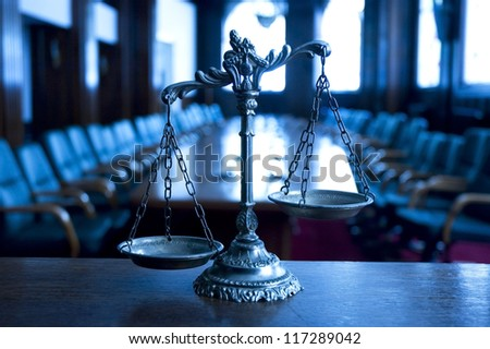 Symbol of law and justice in the empty courtroom, law and justice concept, focus on the scales, blue tone - stock photo