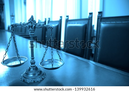 Symbol of law and justice in the empty courtroom, law and justice concept, focus on the scales, blue tone