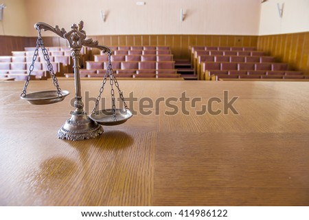 Symbol of law and justice in the empty courtroom, law and justice concept, focus on the scales - stock photo