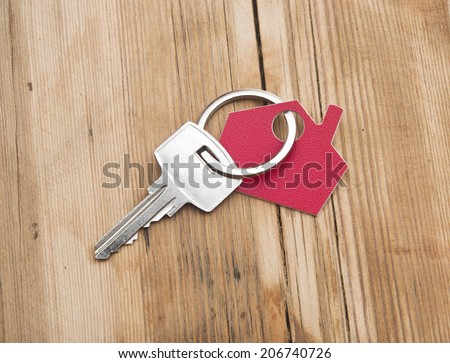 Symbol of the house with silver key on vintage wooden background  - stock photo