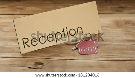 Symbol of the house with silver key on wooden reception desk  - stock photo