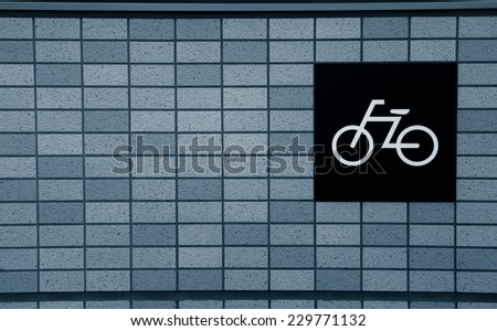 Symbol on the brick wall showing biking trail - stock photo