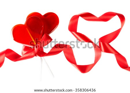 Symbol Valentine's Day: lollipops associated ribbon and heart of twisted ribbons on a white background - stock photo