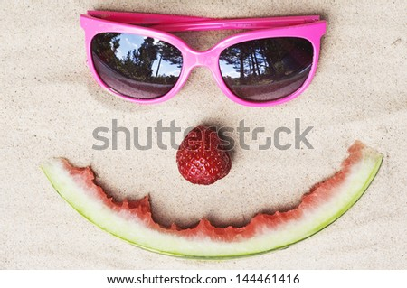 Symbolic happy summer face, made out of fruit and glasses in the white sand - stock photo