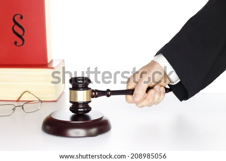 symbolic judgement with gavel in hand and books  - stock photo