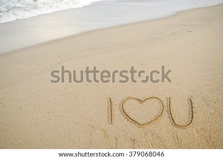 symbols drawn on sandy beach. i love you.  - stock photo