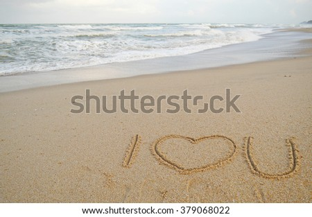 symbols drawn on sandy beach. i love you. low angle view towards the shoreline.