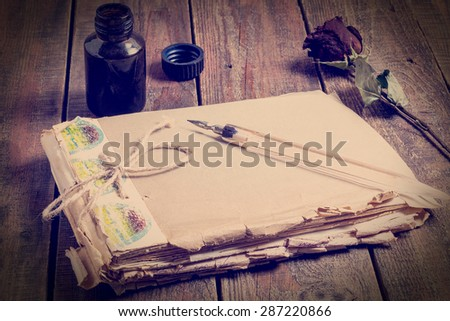 Symbols memories of the past: the old battered notebook, pen and ink in the bottle and dried rose on a wooden table. Tinted photos - stock photo