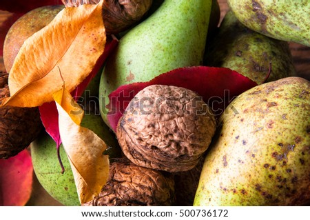 Symbols of autumn - pears, walnuts and withered leaves. Top view