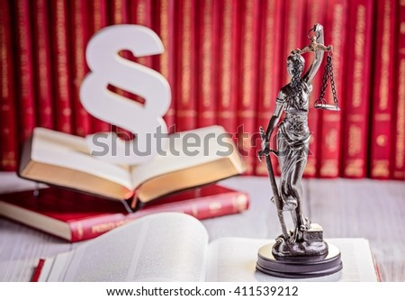 Symbols of law in court library. Wooden paragraph, goddess of justice Themis and legal codes. Law concept - stock photo