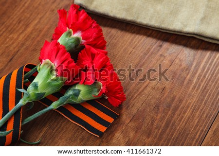 Symbols of Victory in Great Patriotic War three red flower and Soldier's forage cap on a table.  selective focus image - stock photo