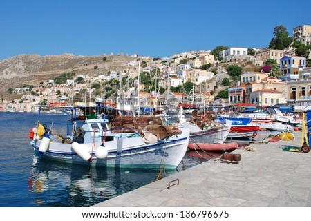 SYMI, GREECE - JUNE 17: Fishing boats moored in Yialos harbour on June 17, 2011 on Symi island, Greece. Yialos, the main harbour on Symi,  is a popular destination for day trips from nearby Rhodes.