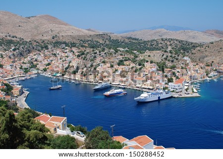 SYMI, GREECE - JUNE 19: Looking down onto boats moored in Yialos harbour on June 19, 2011 on Symi island, Greece. Yialos is a popular destination for day trippers from Rhodes island. - stock photo