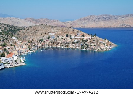 SYMI, GREECE - JUNE 19, 2011: Looking down onto Yialos harbour on the Greek island of Symi. The island is a popular destination for day trippers from Rhodes and nearby Turkey. - stock photo