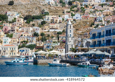 SYMI, GREECE - JUNE 12,2015: The main street along the coast in Yialos harbour on June 12, 2015 on Symi island, Greece. Symi is easy and most popular destination for day tripping from Rhodes island. - stock photo