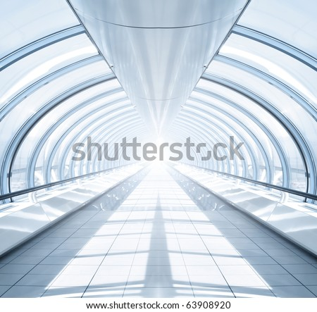 symmetric modern hall inside airport with light in the end of tube - stock photo