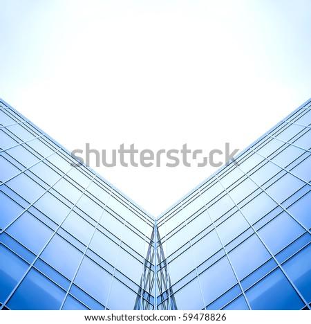 symmetric wall of glass building in haze - stock photo