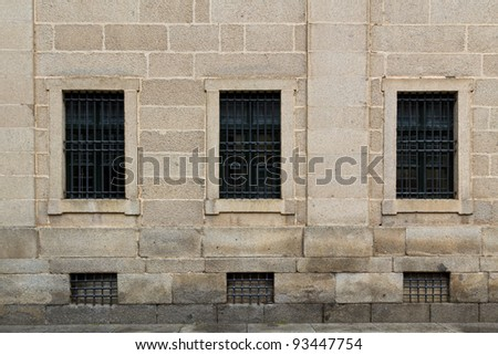 Symmetric windows on in an old wall in El Escorial, a famous spanish monastery - stock photo