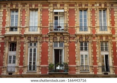 Symmetrical red facade of parisian building (Place des Vosges) - stock photo