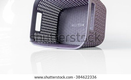 Symmetrical shaped plastic woven laundry basket on empty background. Slightly de-focused and close-up shot. Copy space.