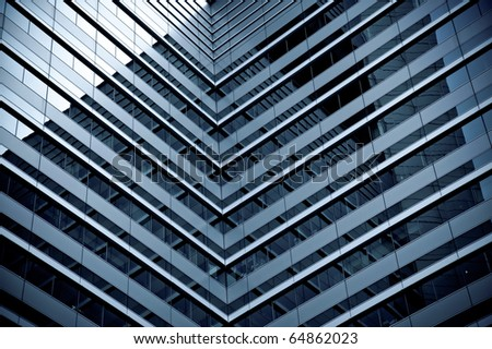 Symmetry in a modern glass-fronted office tower - stock photo