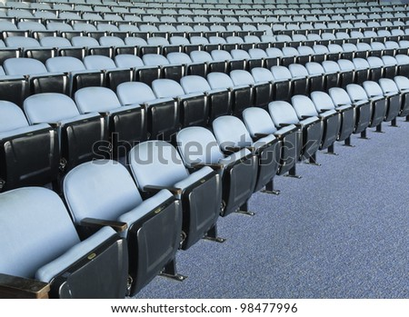 Symmetry in seating for a small crowd: Rows of folding seats in auditorium - stock photo