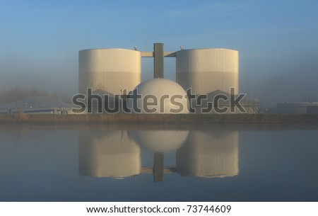 Symmetry of waste water treatment plant in the morning fog. - stock photo