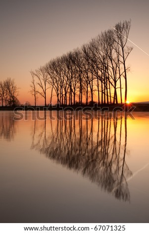 Symmetry reflection on the autumn river - stock photo