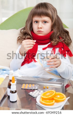 Sympathetic little sick girl wrapped in red scarf is taking a pill and a salver with pills, sprays and orange on the blanket in the bed - stock photo