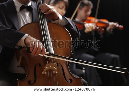 Symphony concert, a man playing the cello, hand close up - stock photo