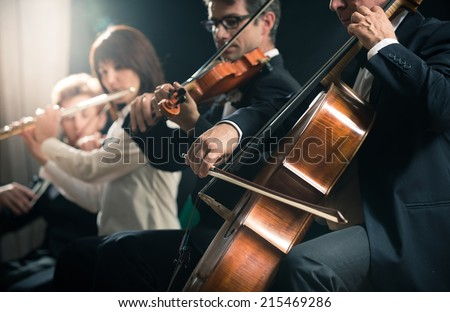 Symphony orchestra on stage, violins, cello and flute performing. - stock photo