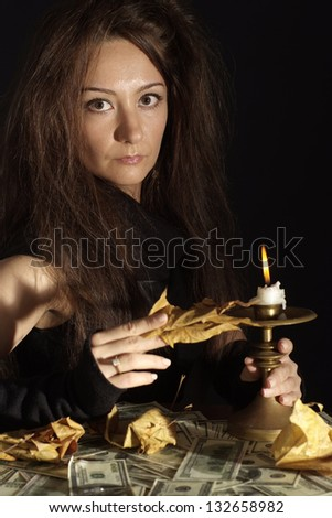 Sympothetic girl as a witch on a dark background - stock photo