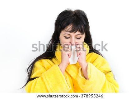 Symptoms and treatment of colds, influenza, fever. Treatment of allergy. A cold woman sneezing into a handkerchief on a white background.