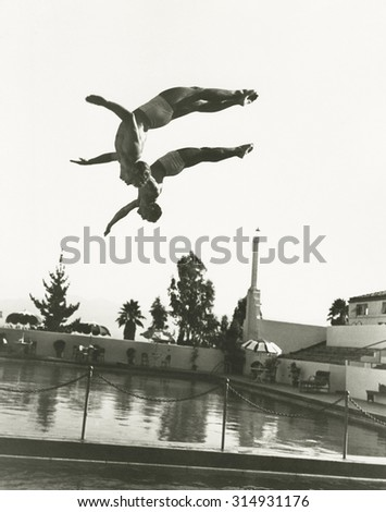 Synchronized divers in mid-air - stock photo