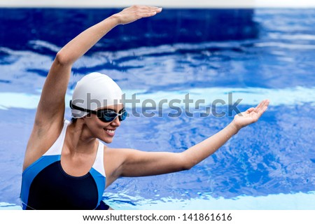 Synchronized female swimmer stretching at the pool - stock photo